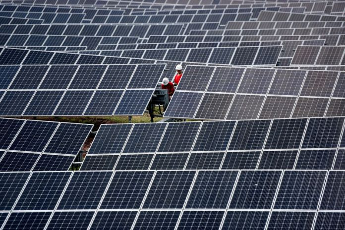 © Reuters. FILE PHOTO: Workers inspect solar panels at a photovoltaic power station on a hill in Linyi