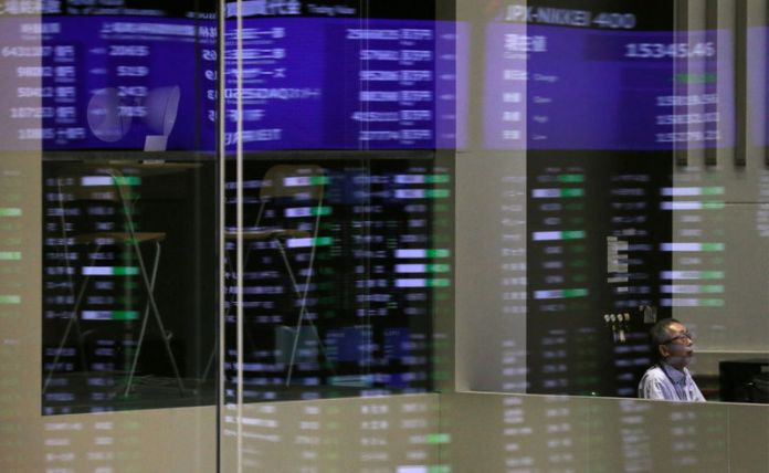 © Reuters. FILE PHOTO: Market prices are reflected in a glass window at the TSE in Tokyo