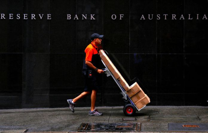 © Reuters. FILE PHOTO: A worker delivering parcels pushes a trolley past the Reserve Bank of Australia building in central Sydney, Australia