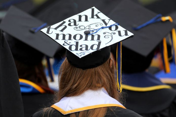© Reuters. FILE PHOTO: Messages and artwork are pictured on the top of the caps of graduating students during their graduation ceremony at UC San Diego in San Diego