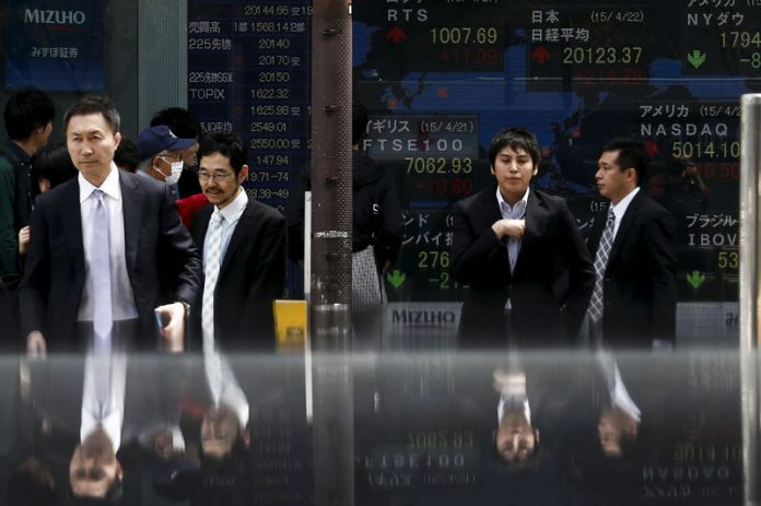 © Reuters. FILE PHOTO: People walk in front of board displaying stock indexes  in Tokyo