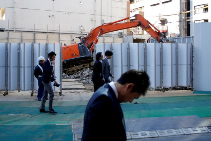 © Reuters. FILE PHOTO: Businessmen walk past heavy machinery at a construction site in Tokyo's business district