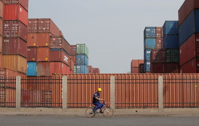© Reuters. A worker cycles past containers outside a logistics center near Tianjin Port