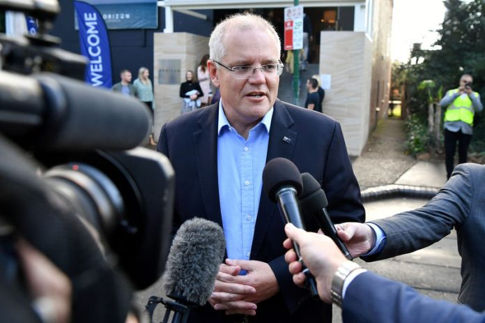 © -. Australian Prime Minister Morrison speaks to the media as he arrives at the Horizon Church in Sutherland