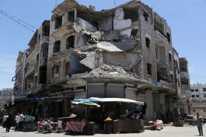 © -. People walk past a damaged building in the city of Idlib