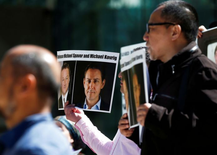 © -. FILE PHOTO: People hold signs calling for China to release Canadian detainees Michael Spavor and Michael Kovrig during a court appearance by Huawei's Financial Chief Meng Wanzhou, outside of British Columbia Supreme Court building in Vancouver, British Col