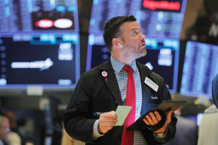 © -. Traders work on the floor of the New York Stock Exchange shortly after the opening bell in New York
