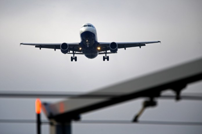 © -. FILE PHOTO: An airplane prepares to land at Cointrin airport in Geneva