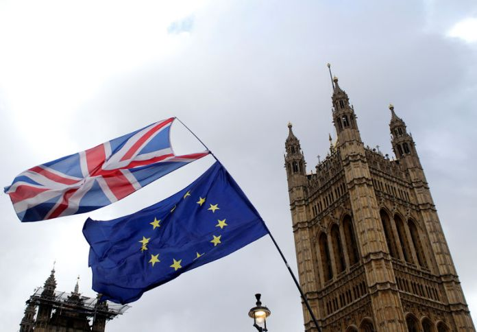 © -. Flags flutter outside the Houses of Parliament in London