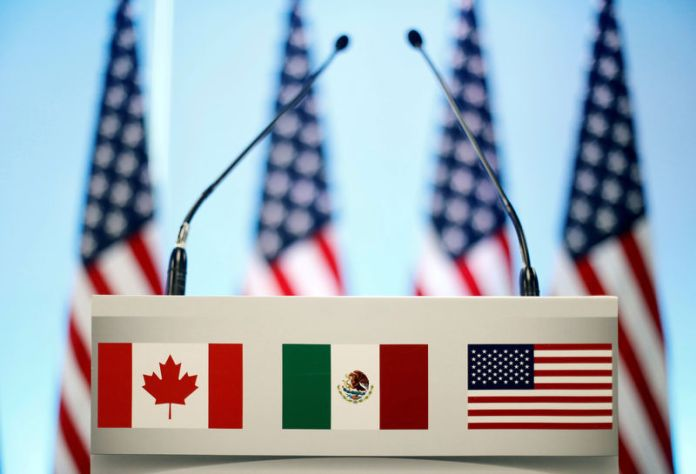 © -. FILE PHOTO: The flags of Canada, Mexico and the U.S. on a lectern before a joint news conference on the closing of the seventh round of NAFTA talks in Mexico City