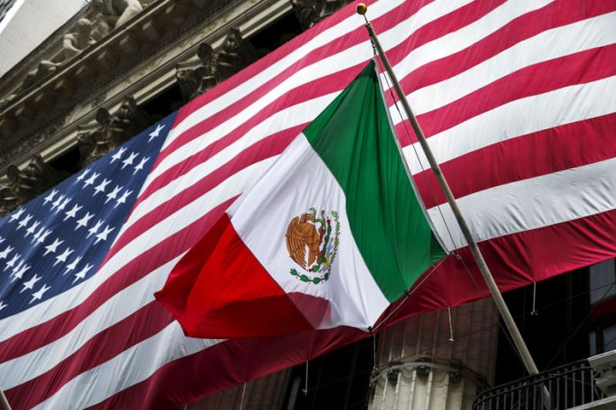 © -. FILE PHOTO: The flag of Mexico changes in front of a large U.S. flag in front of the New York Stock Exchange
