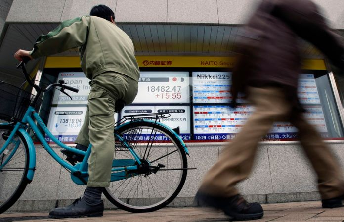 © -. A man riding on a bicycle looks at an electronic board showing the Japan's Nikkei average outside a brokerage in Tokyo