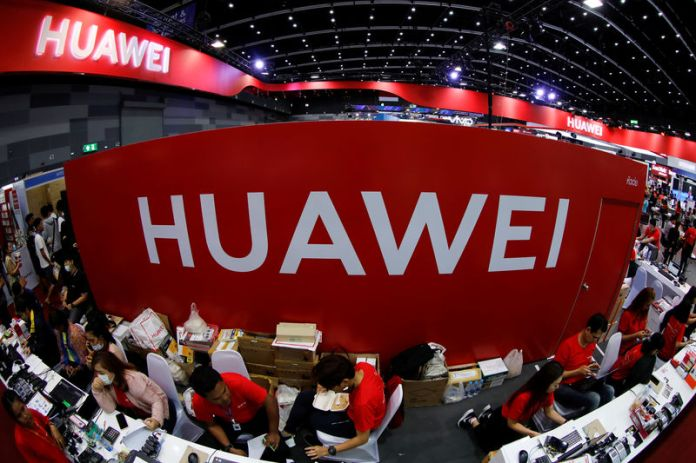 © -. FILE PHOTO: Workers sit at the Huawei stand at the Mobile Expo in Bangkok
