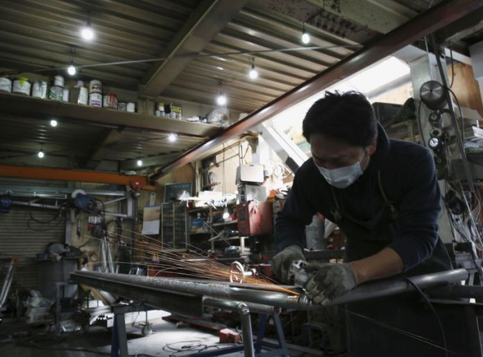 © -. An engineer makes an arm rail for residential buildings inside a metal processing factory at an industrial zone in downtown Tokyo