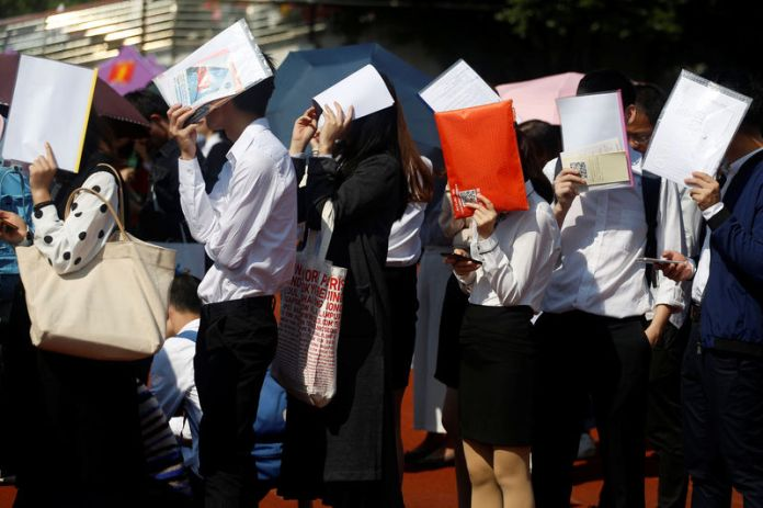 © -. Students shield themselves from the sun as they line up at a job fair at a university in Guangzhou