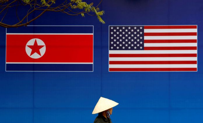 © -. FILE PHOTO: A person walks past a banner showing North Korean and U.S. flags ahead of the North Korea-U.S. summit in Hanoi