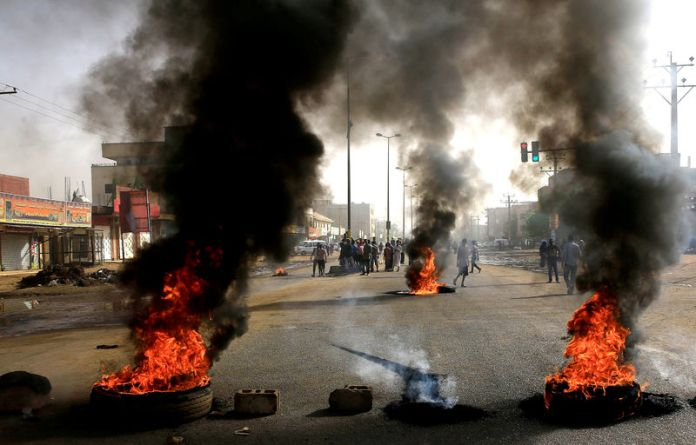 © -. Sudanese protesters use burning tyres to erect a barricade on a street, demanding that the country's Transitional Military Council hand over power to civilians, in Khartoum