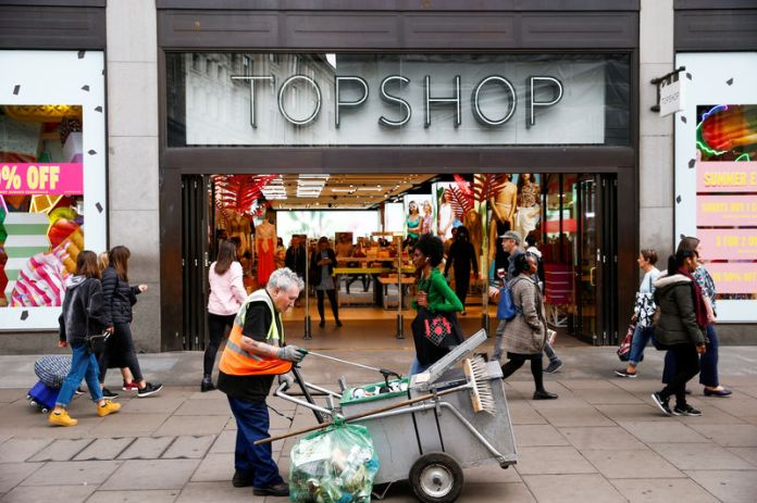© Reuters. People walk past a Topshop and Topman store, owned by Arcadia Group, in central London