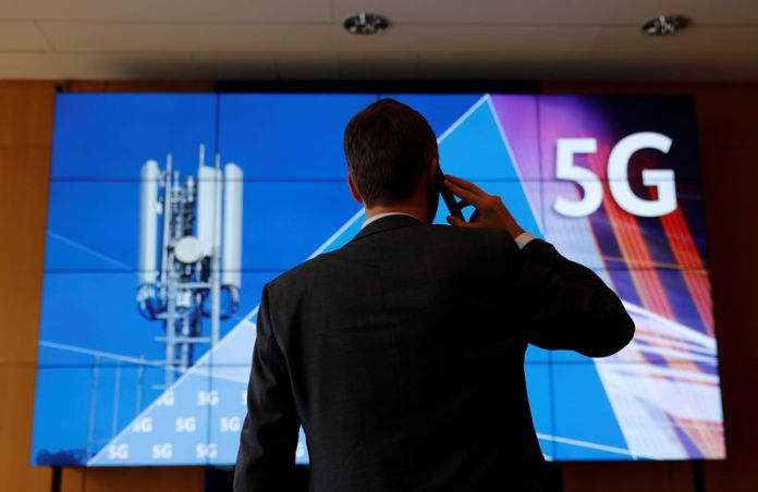 © -. An employee of Germany's Federal Network Agency (Bundesnetzagentur) uses his mobile phone in front of a screen set up for the auction of spectrum for 5G services at the Bundesnetzagentur headquarters in Mainz