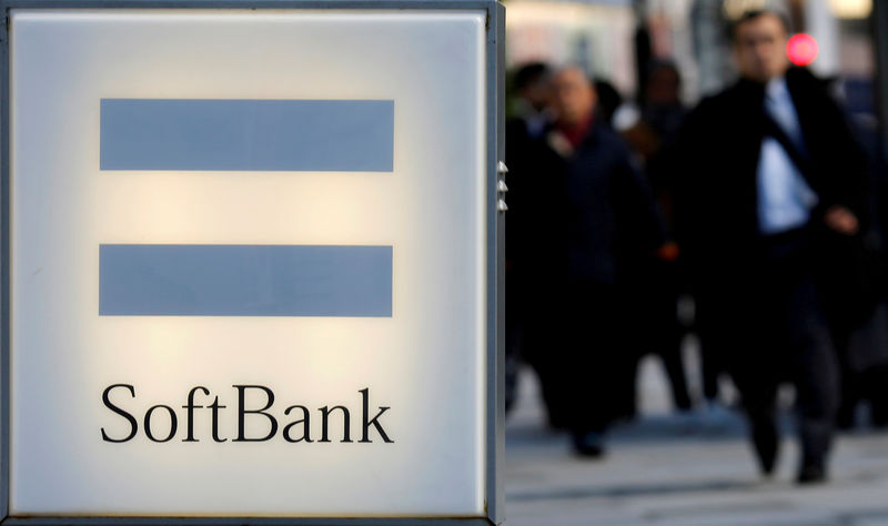 © Reuters. FILE PHOTO: People walk near the logo of SoftBank Corp in Tokyo