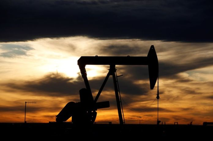 © Reuters. FILE PHOTO: The sun sets behind an oil pump cylinder on a drilling platform in the Permian Basin in Loving County