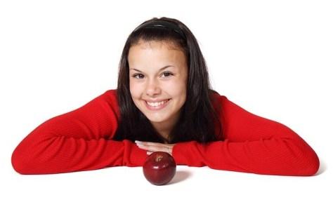 Chica sonriente con una manzana.