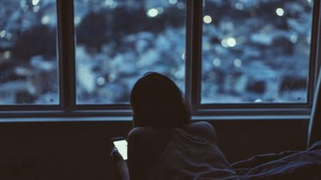 Mujer con celular y escasa luz