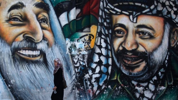 A Palestinian student walks in front of a mural depicting the late Palestinian leader Yasser Arafat, right. A team of experts opened Arafat's grave last November, and took samples from his body to seek evidence of alleged poisoning.