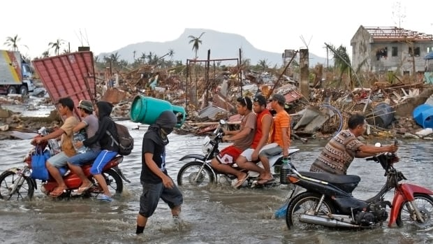 People commute through a flooded street amidst the rubble after a downpour in the aftermath of super typhoon Haiyan in Tacloban city, central Philippines November 14, 2013. Philippine President Benigno Aquino was under growing pressure on Thursday to speed up the distribution of food, water and medicine to desperate survivors of a powerful typhoon and to revive paralysed local governments.