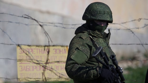 A Russian soldier guards a pier where two Ukrainian naval vessels are moored, in Sevastopol, Ukraine, on Wednesday, March 5, 2014. The Canadian government has ordered nine Russian soldiers participating in military exercises to leave Canada by end of day Friday.