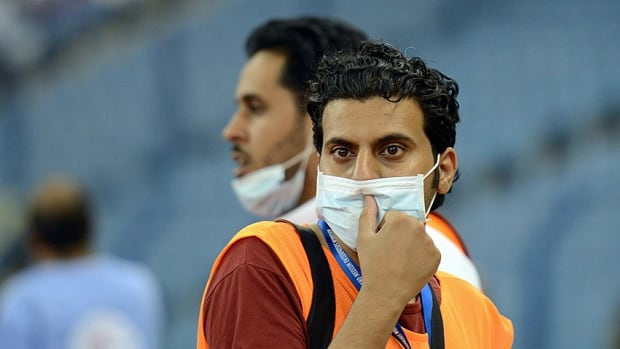 Saudi photographers wear masks during a football match on April 22, 2014 in Riyadh. As MERS, the SARS-like virus, continues to kill more people in the kingdom, Egypt has reported its first case of the virus on Saturday.