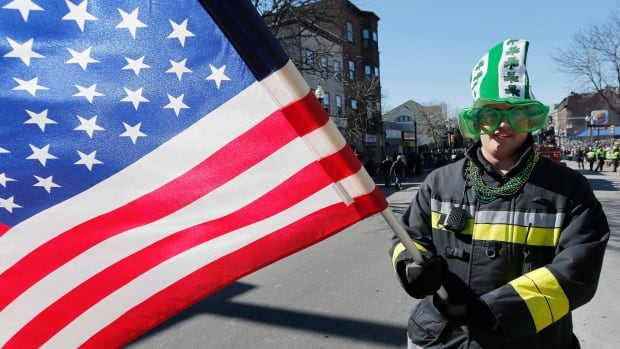 A reveller marches in the St. Patrick's Day parade in Boston. The parade tradition was born in New York City in the 1700s, then later adopted by Ireland and around the world.
