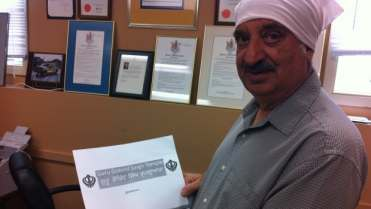 Narinder Singh Pawar, president of the Guru Gobin Singh Temple Association in Prince George, holds an example of a street sign that would include English and Punjabi.