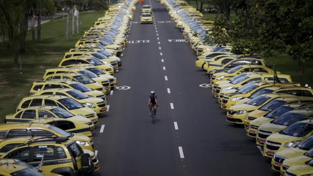 A man rides his bicycle between taxis parked on the street during a protest against Uber in Rio de Janeiro, Brazil on July 24, 2015. A number of protests have cropped up the world over as the ride-hailing app grows in popularity.