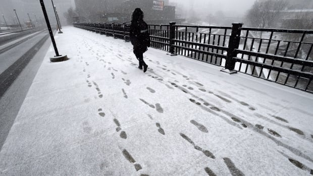 A pedestrian makes her way through the snow in Ottawa back in April. With December looming, Environment Canada is forecasting 'early season significant snowfall' for Sunday and Monday.