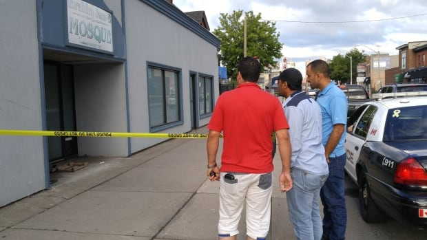 Three men stand outside the Ibrahim Jame Mosque on Thursday September 15, 2016 hours after, police say, a man was charged with arson after setting fire to the entrance of the mosque.