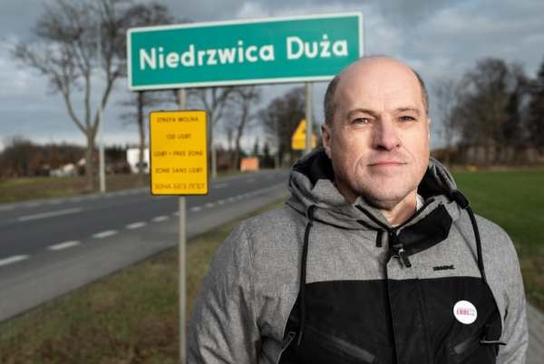 Person wearing a grey and black jacket, standing in front of a sign reading 'Niedrzwica Duza' and a 'LGBT free zone' sign in Poland