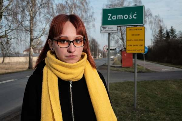 Person wearing orange eye shadow and a yellow scarf, standing in front of a town sign and a 'LGBT free zone' sign in Poland.