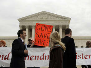 "A pro-gun advocate holds up a sign outside the Supreme Court in Washington, as the court heard arguments in an attempt to overturn the District of Columbia's firearms ban. The District of Columbia is asking the Supreme Court to preserve the capital's ban on handguns in a major case over the meaning of the Second Amendment's ""right to keep and bear arms."