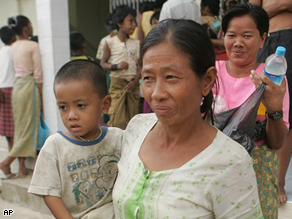 Victims of Cyclone Nargis smile as they receive donated goods from a local donor at a monastery outside the capital of Yangon, Myanmar on Monday May 19, 2008.