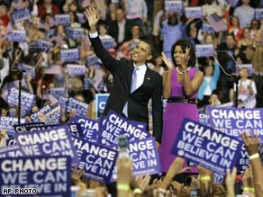 Obama and his wife Michelle wave to supporters at a primary night rally in St. Paul, MN.