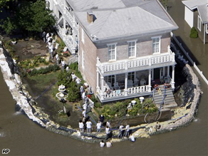 Volunteers work to protect a home from the rising flood waters of the Mississippi River Thursday, June 19 in Clarksville, Mo.