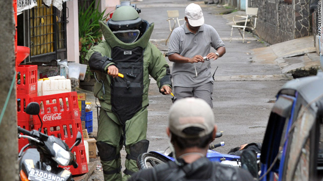 An Indonesian bomb squad officer checks out the bodies of suspected terrorists killed in a shootout near Jakarta.