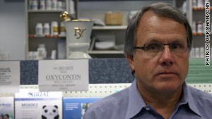 Pharmacist Bill McNary stands in front of a sign telling would-be robbers that he has no OxyContin in stock.