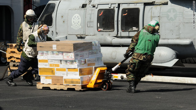 Sailors move food and other supplies across the USS Ronald Reagan's flight deck for earthquake and tsunami victims in Japan.