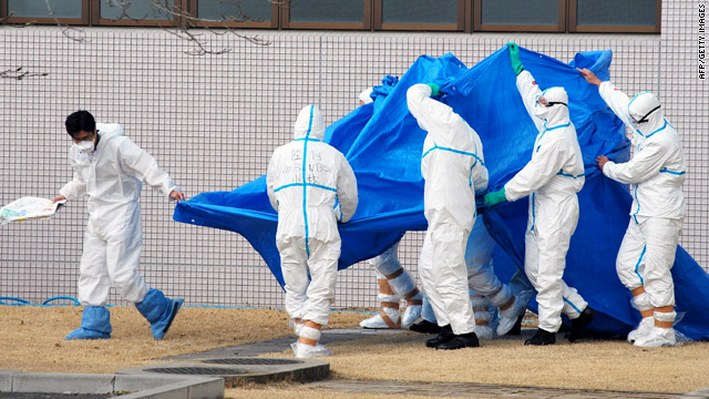Military officers on Friday hold a blue sheet over people exposed to high levels of radiation at Japan's Fukushima Daiichi plant.