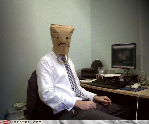 Man bored in office wearing a paper bag on his head.