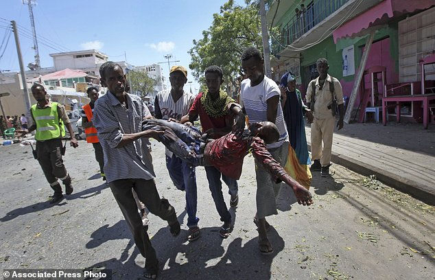 Rescuers carry away a man who was wounded in a car bomb attack in Mogadishu, Somalia Monday, March 13, 2017. A suicide car bomber detonated near the Weheliye hotel in the capital Monday morning, killing a number of people on the busy Maka Almukarramah road, police said. (AP Photo/Farah Abdi Warsameh)