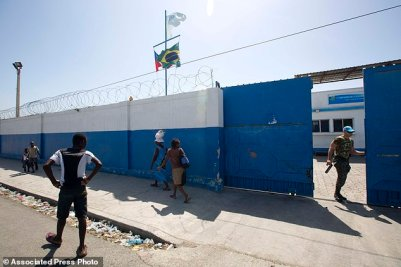 A Brazilian U.N. peacekeeper opens a gate at the U.N. base in the Cite Soleil slum of Port-au-Prince, Haiti