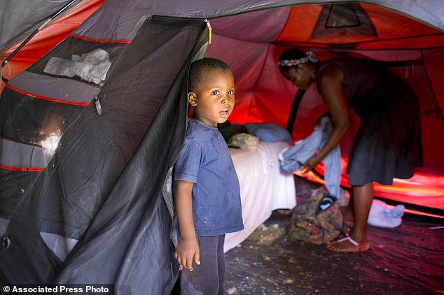 Marlene Andre 38, background right, arranges clothes while her son, Johnsley, 5, stands in front of their tent in Jacmel, Haiti. Marlene was barely scraping by before a U.N. peacekeeper made her pregnant